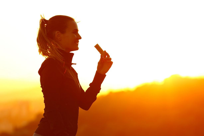 中区上前津パーソナルジム_夕日を背景にプロテインバーを食べる女性の上半身