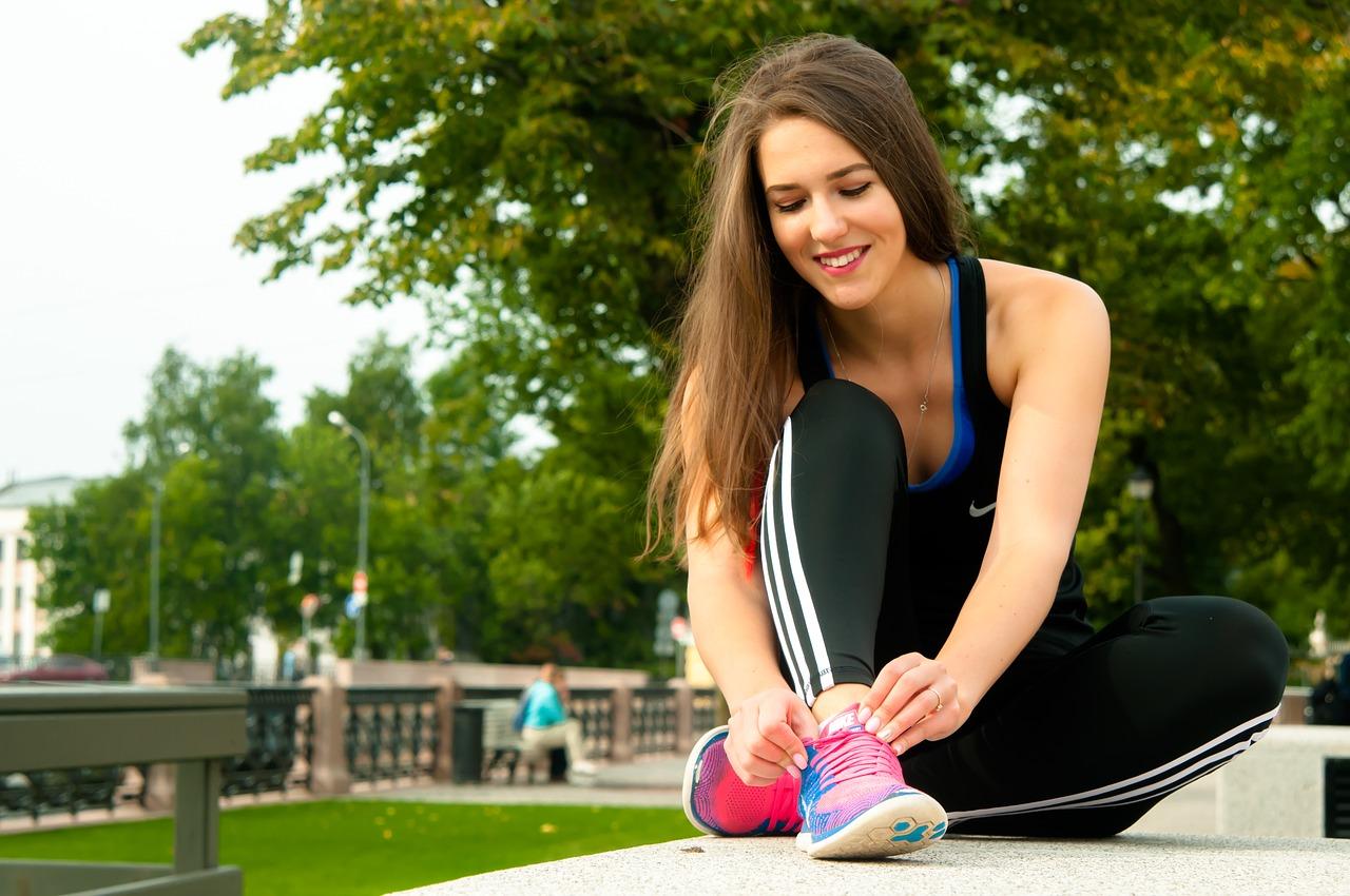 女性が公園で運動する前に靴紐を結んでいます