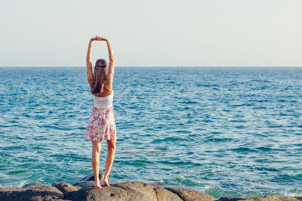 女性が海を見ながら伸びをしている写真