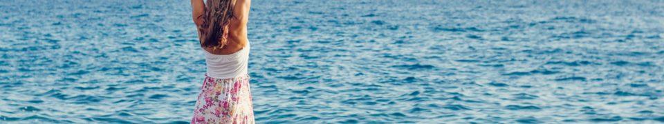 女性が海を見ながら両手を上げて伸びをしている写真
