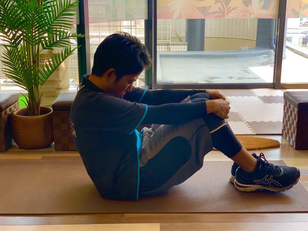 トレーナーが反り腰改善のストレッチ運動をしている写真