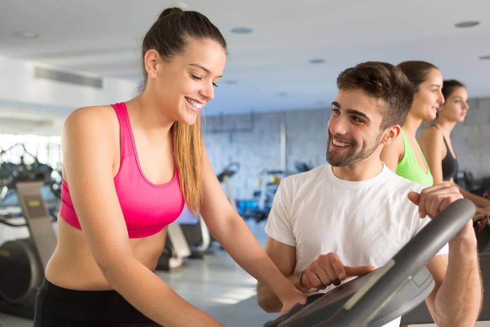 スポーツジムで女性が男性に教えられながれエアロバイクでトレーニングをしています