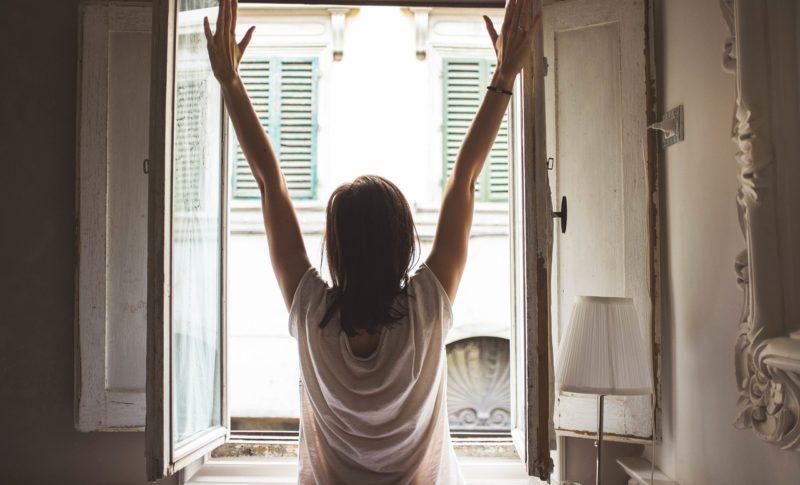女性が窓を開けて気持ち良く伸びをしている写真