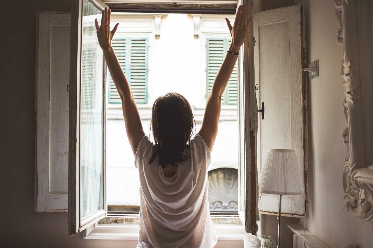 女性が窓を上げて気持ち良く伸びをしている写真