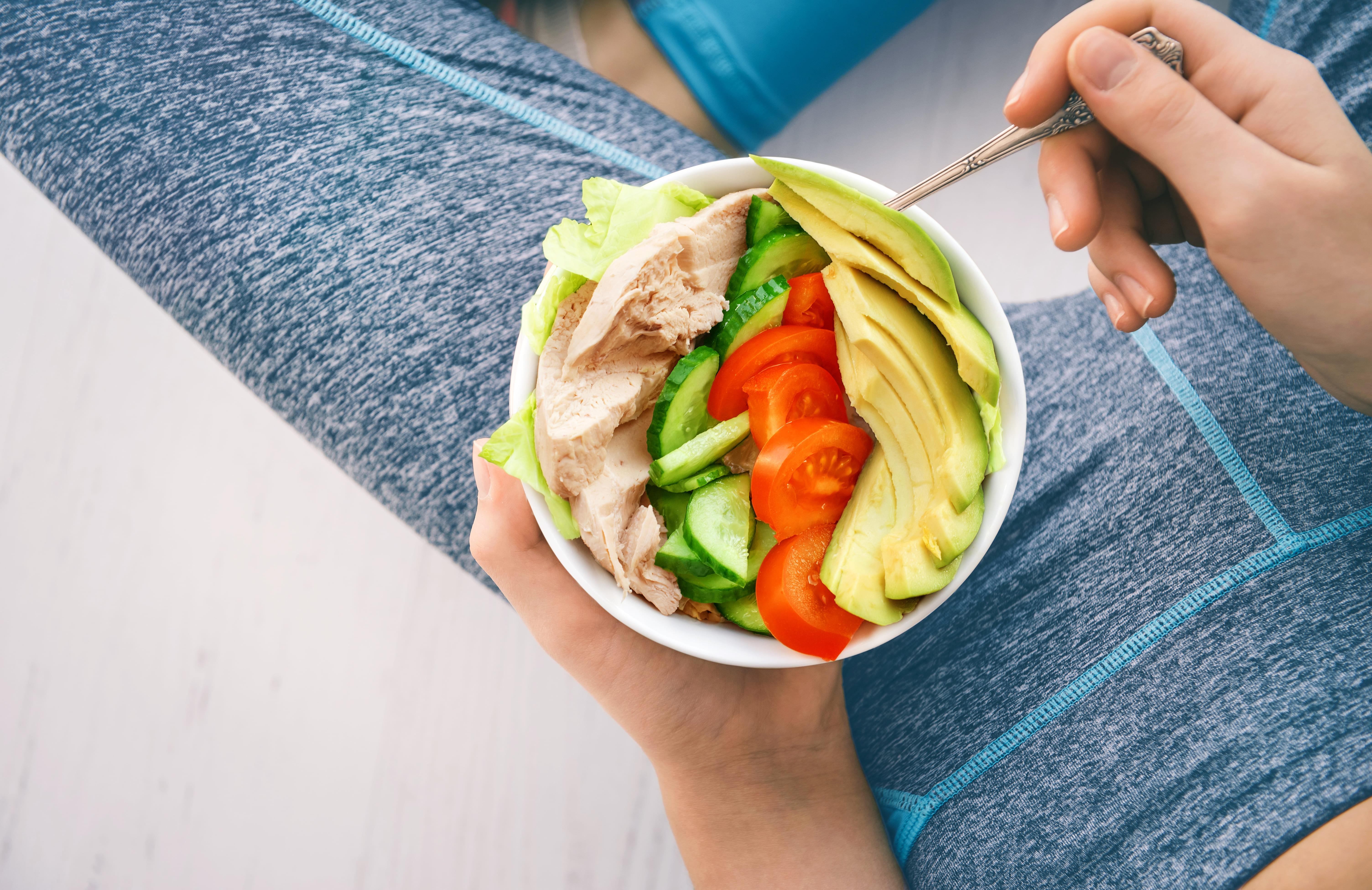 鶏肉、きゅうり、アボカド、トマトのサラダを持った女性の写真