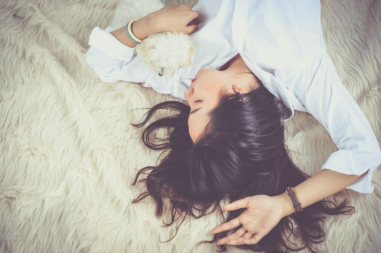 女性が犬を抱いて寝ている写真