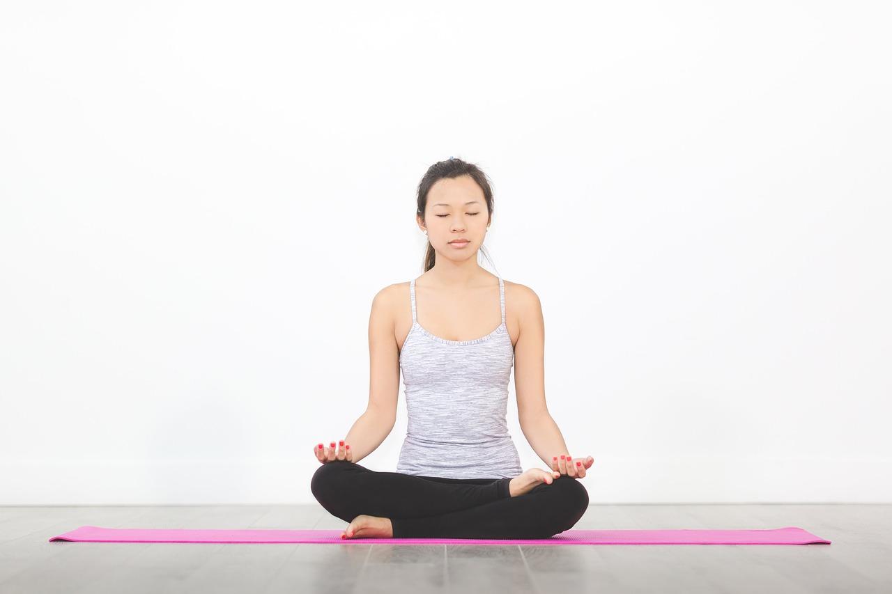 女性が座ってヨガの呼吸をしている写真