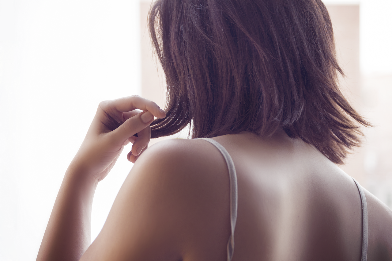 女性の肩甲骨から上の後ろ姿の写真