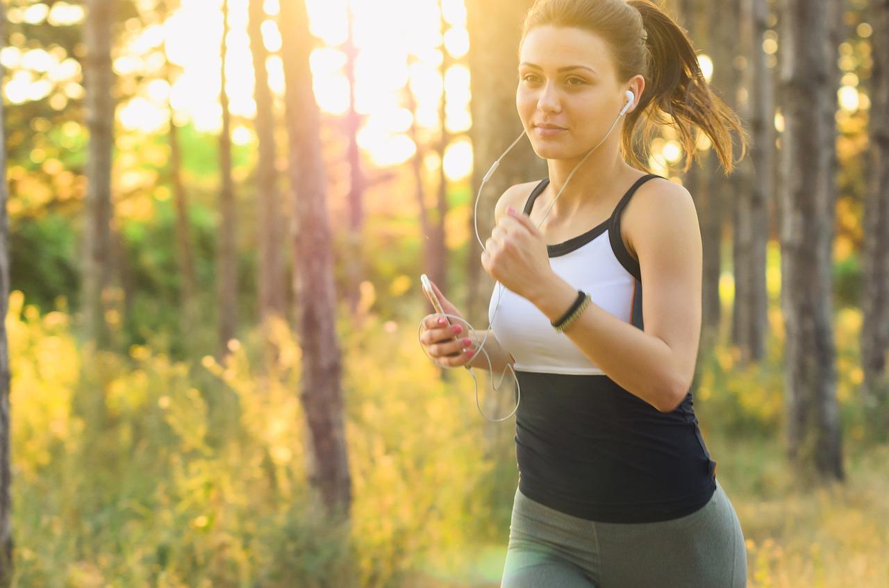 森林の中で女性が音楽を聴きながら有酸素運動