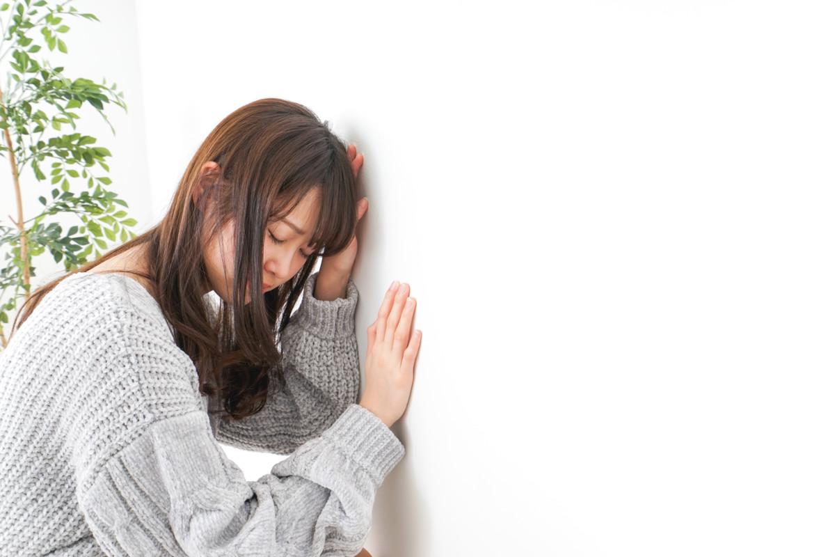 女性が壁に手をついて落ち込んでいる写真