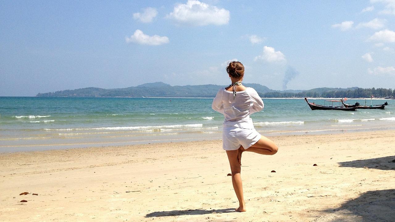 砂浜でヨガのポーズをして海を見ている写真
