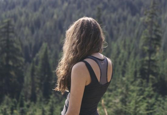 女性が目の前に広がる森を見ている写真