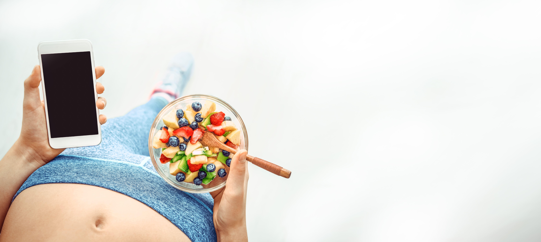 携帯とダイエット食事を持った女性の写真