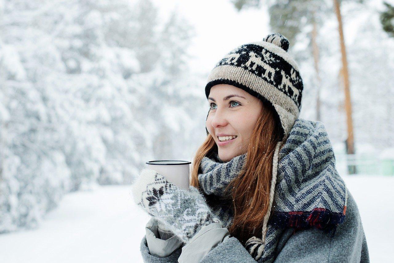 女性が雪の中で温かい飲み物を飲んでいる写真