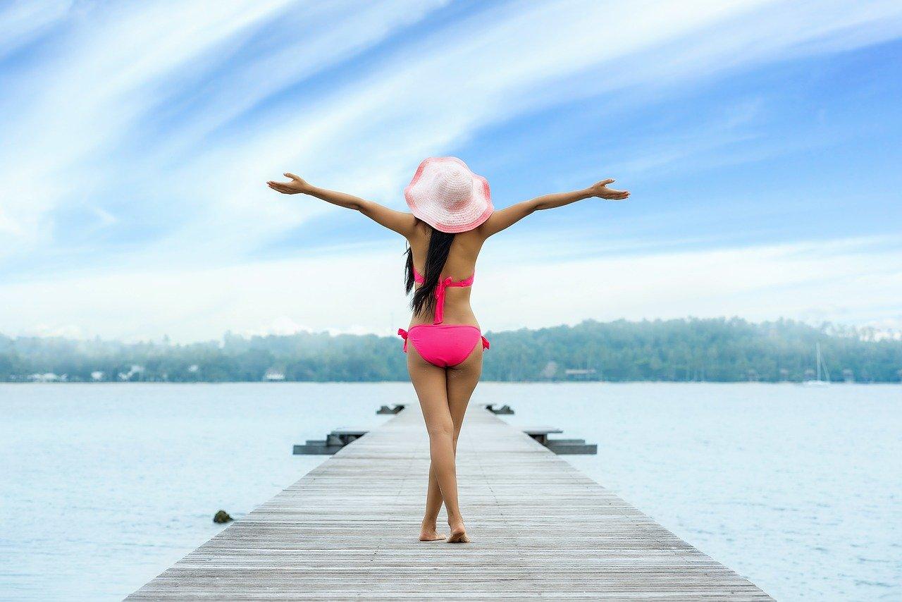 女性が海にある桟橋の上で手を広げている写真