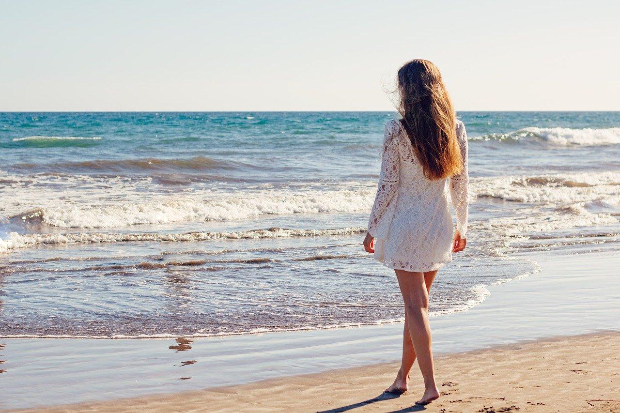 女性が砂浜で海を見ている写真