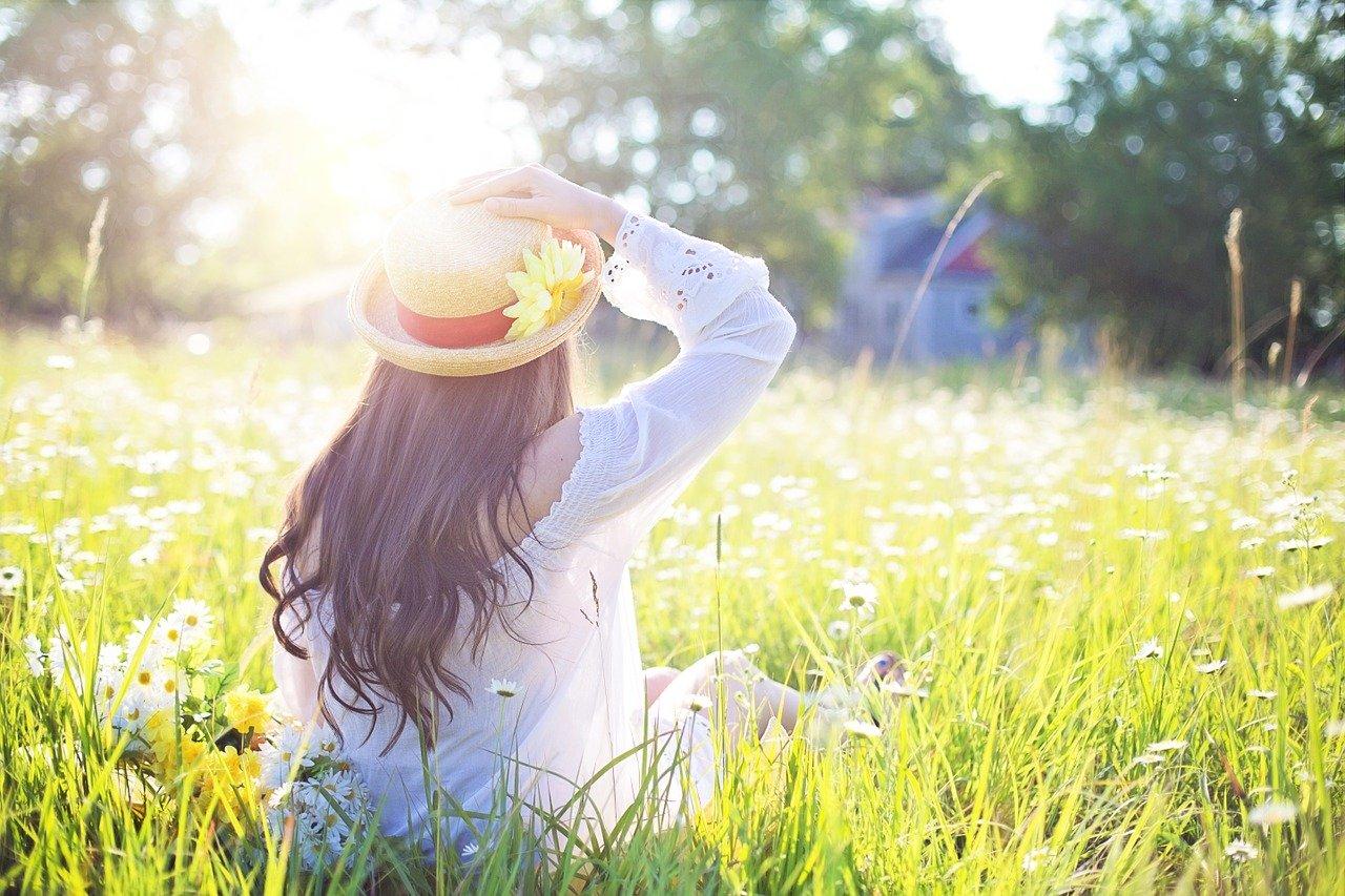 お花畑の中に少女が座っている写真