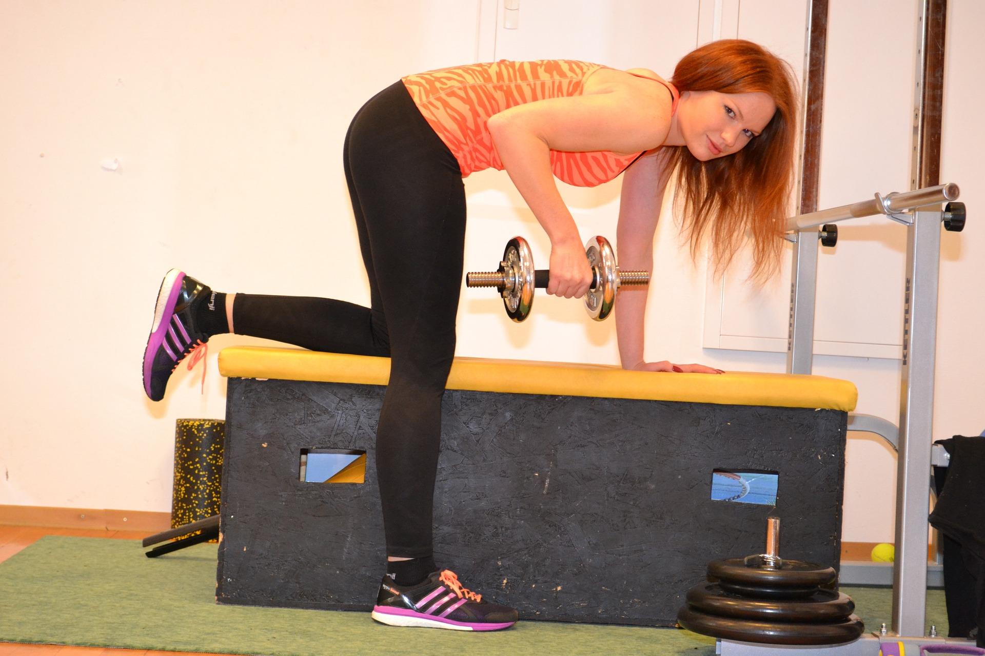 女性がベンチに片手、片足をつけながらトレーニングをしている