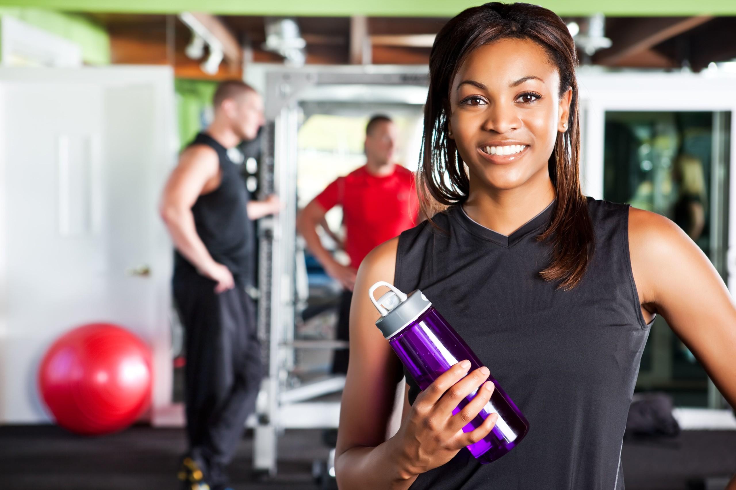 女性が水筒を持ちながら笑顔で写真を取っている。