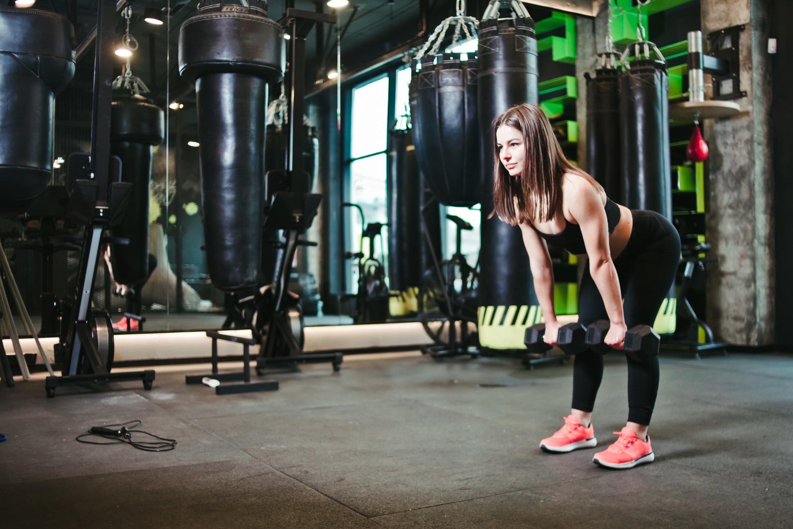 天白区パーソナルジムで女性がダンベルを持ってダイエットトレーニングを行なっている