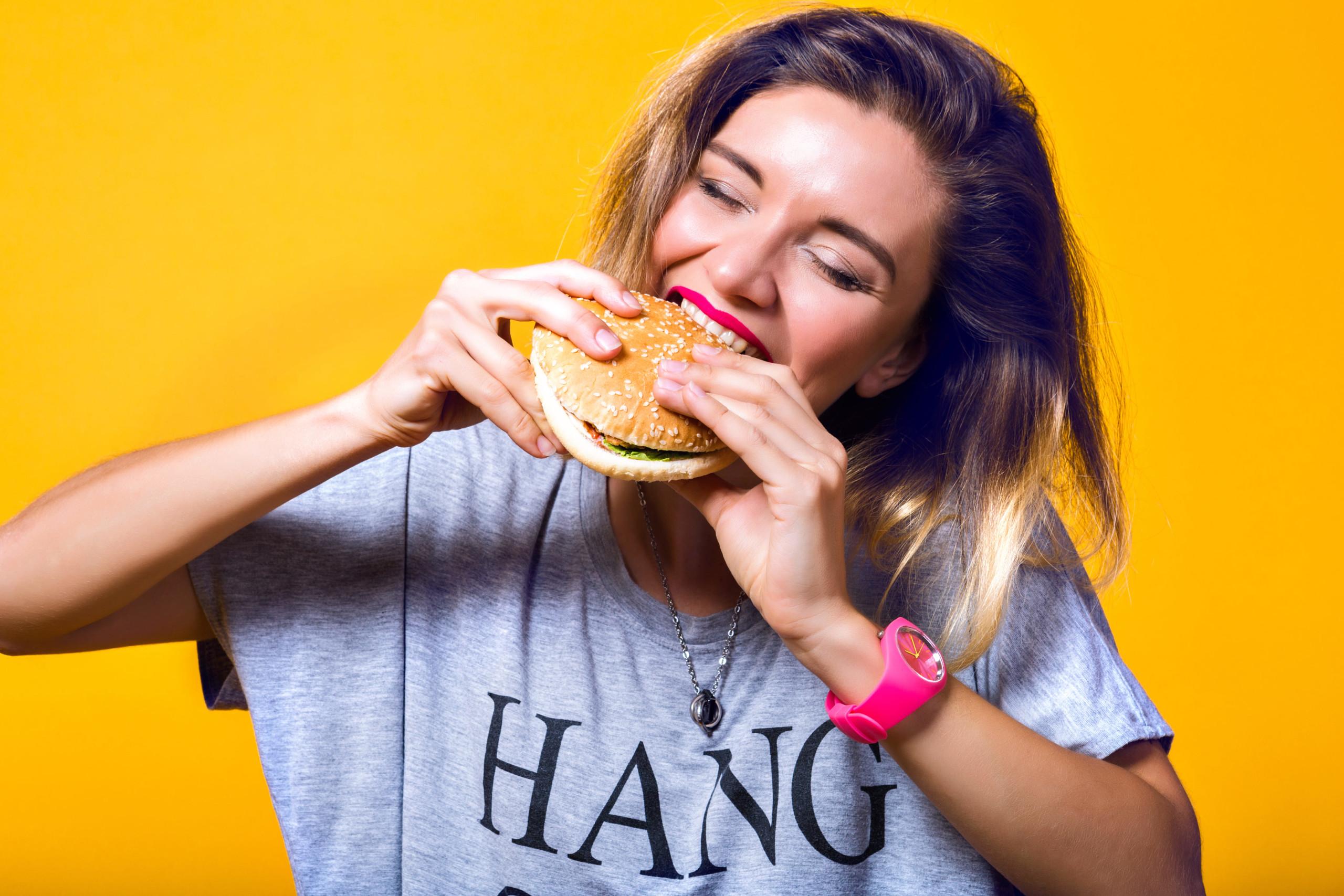 女性がハンバーガーを美味しそうに食べている