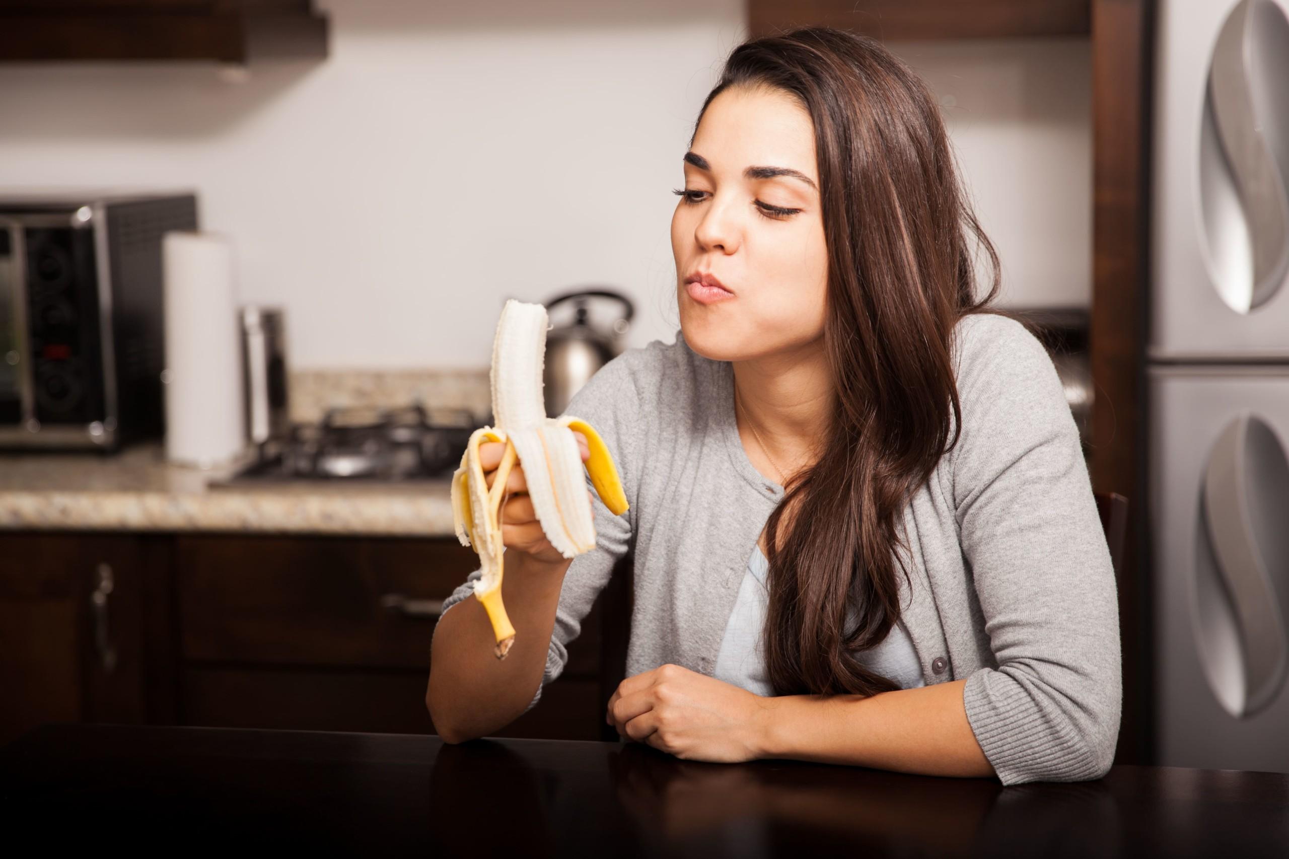 女性が台所でバナナを食べている