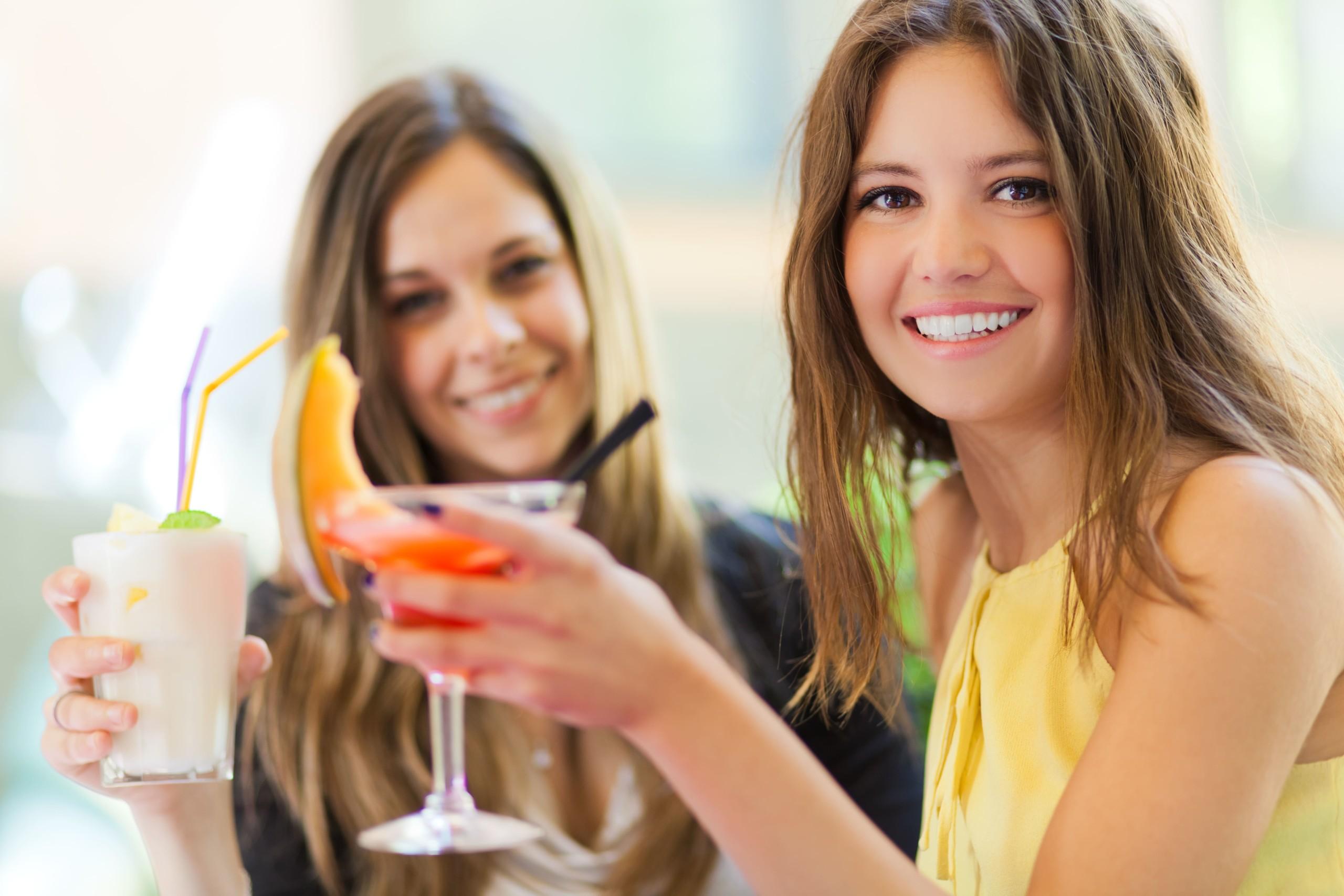 女性二人がお酒を楽しそうに飲んでいる