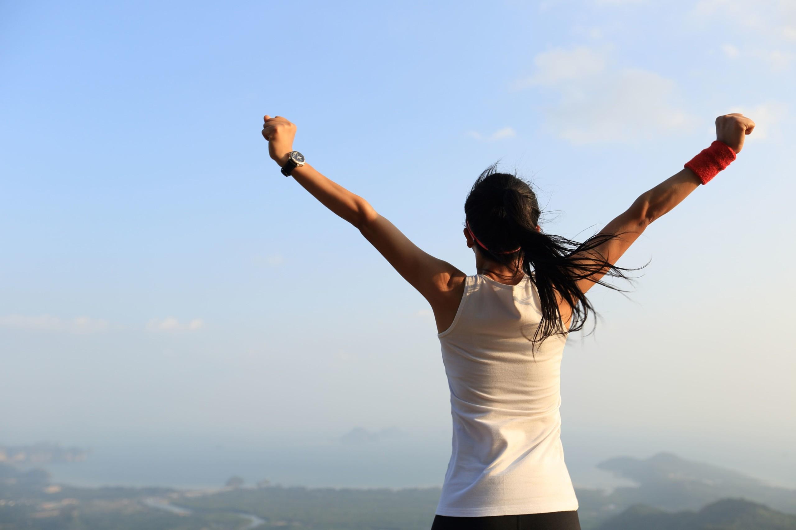 女性が山の頂上で両腕を上げている